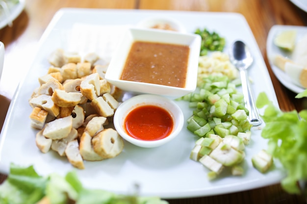 Вьетнамские фрикадельки (nam neung), вьетнамская свиная колбаса и салат.