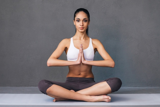 Namaste! beautiful young african woman in sportswear practicing yoga and looking at camera while sitting in lotus position against grey background