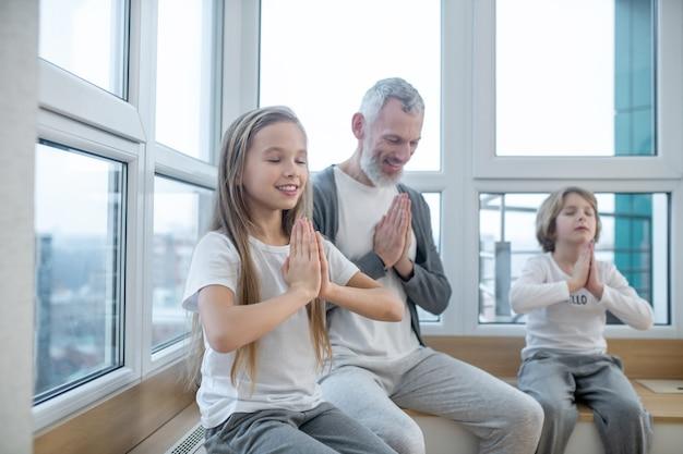 ナマステ。ナマステで平和に座っている白髪の男と彼の子供たち