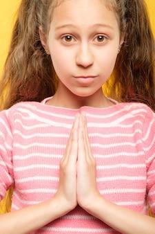 나마스테 무드라. 인사 제스처에 손을 잡고 소녀입니다. 아이 요가 연습 개념.