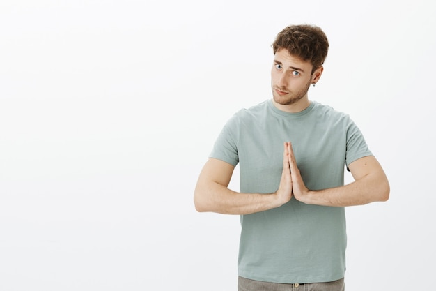 Namaste my friend. handsome polite young man with bristle in earrings, bowing while holding palms in pray and giving greeting to someone
