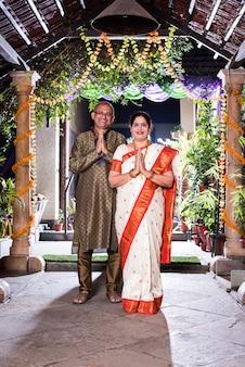 Namaste 또는 namaskara - 디왈리 축제 또는 결혼식에서 손님을 환영하는 인도 부부