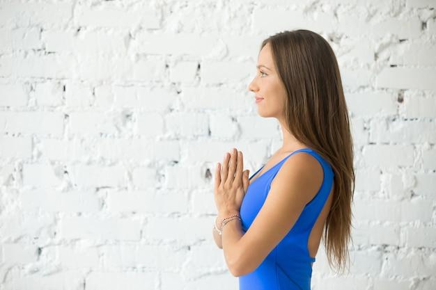 Namasteを作る若い魅力的な女性のプロフィールの肖像