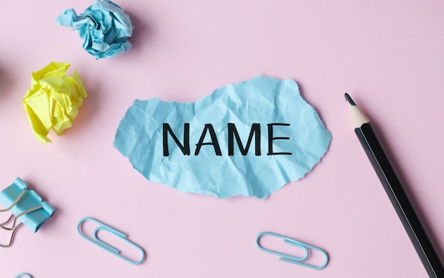 Name text on a crumpled piece of paper with pencil and paper clips.
