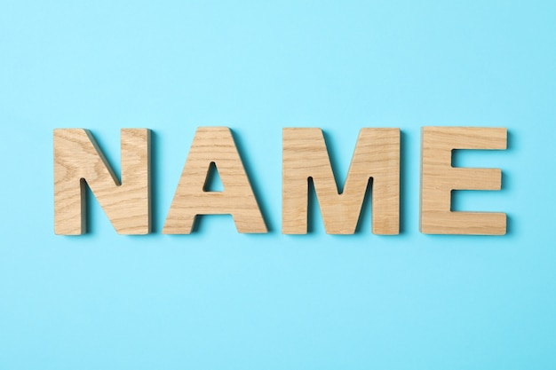 Name word made from wooden letters on blue background