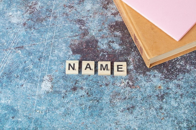 Name writing with black letters on wooden dices with an old book around. high quality photo