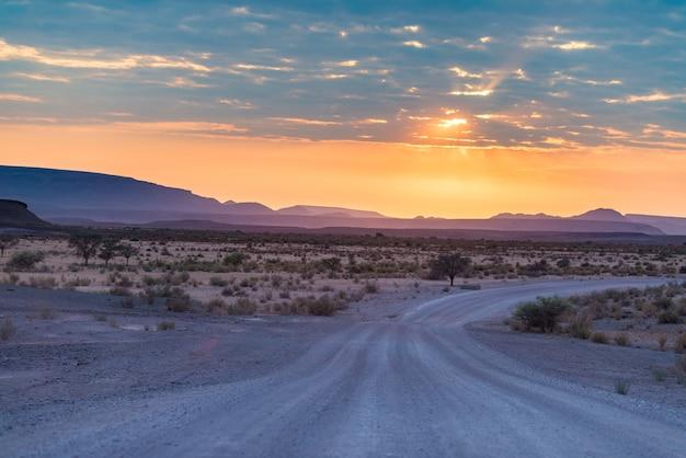 Восход солнца над пустыней namib, roadtrip в чудесном национальном парке namib naukluft, место назначения перемещения в намибии, африке. утренний свет, туман и туман, приключение на бездорожье.