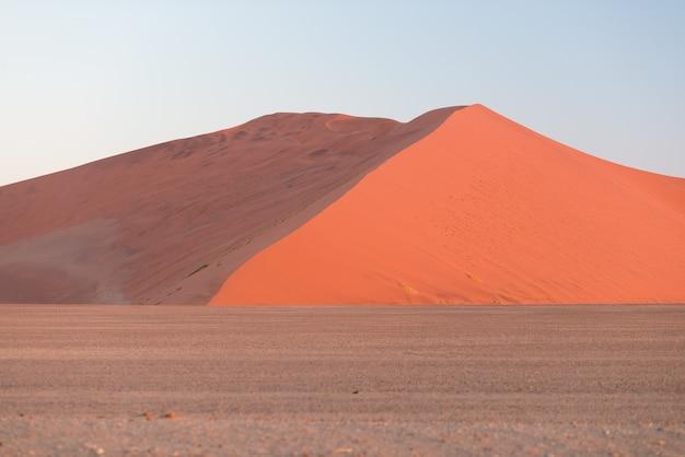 Красочный заход солнца над пустыней namib, намибия, африка. живописные песчаные дюны в подсветке в национальном парке намиб науклуфт