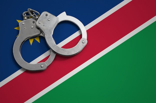 Namibia flag  and police handcuffs. the concept of crime and offenses in the country
