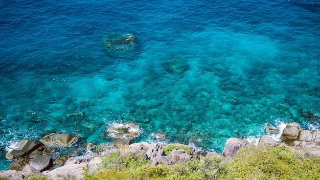 Nangyuan island, west side of the twin peaks island, clear blue water hitting rocks, thailand.