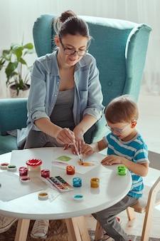 乳母と子供は家で一緒に水彩絵の具を描く