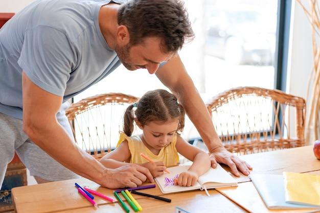 Няня занимается творчеством с маленькой девочкой, наблюдая, как она рисует цветными фломастерами в тетради.