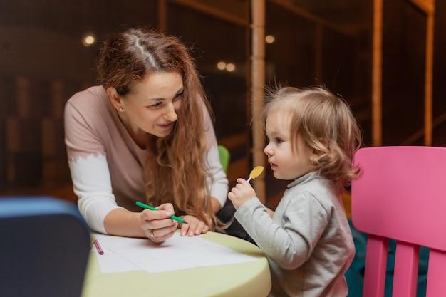 Няня учит маленькую девочку рисовать цветными карандашами, сидя за столиком в детском развлекательном центре.