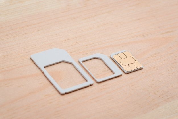 Nano sim card and adapters for different size on wooden table