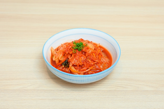 Napa cabbage kimchi in white bowl of side dishes