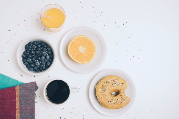 Napkin; blueberry; glass of juice; halved orange; coffee cup and donut on white backdrop
