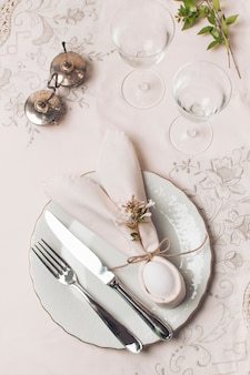Napkin and cutlery on plate near glasses and plant