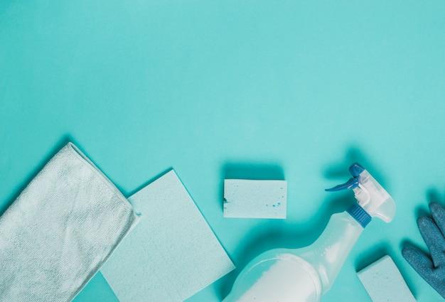 Napkin, duster, sponge and spray bottle on turquoise backdrop