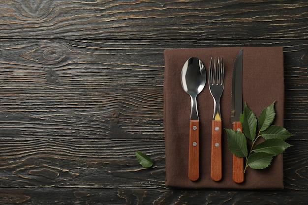 Салфетка, вилка, ложка, нож и лист на деревянном