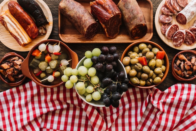 Napkin and grapes near pickles and sausages