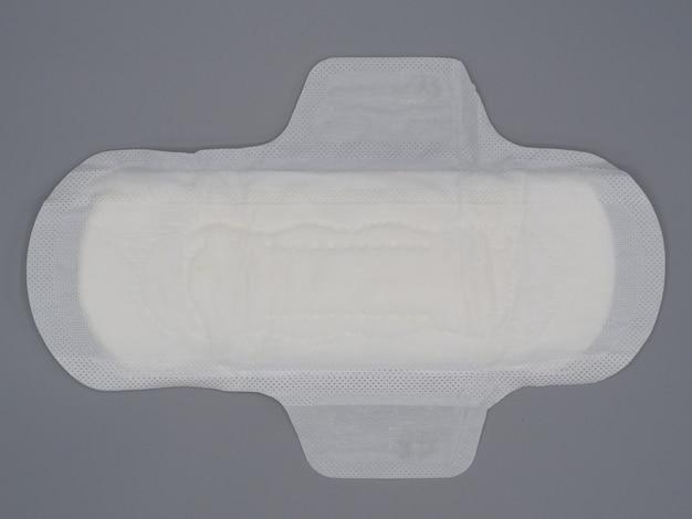 Салфетка санитарная. мягкая и удобная прокладка для гигиенических салфеток и серый фон. белый верхний лист. студия выстрел изолирован. салфетки при менструации. тип крыла на ночь. быстрый поглотитель. хлопок мягкое ощущение.