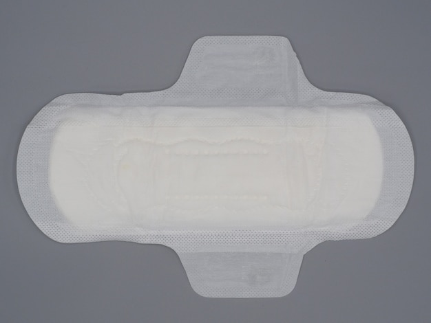 Napkin sanitary. soft and comfort sanitary napkin pad and grey background. white top sheet. studio shot isolated. cloth pads for menstruation. wing type for night. quick absorber. cotton soft feeling.