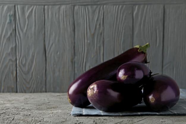 Napkin with fresh eggplants on gray background