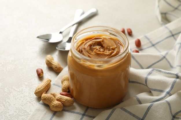 Napkin with peanut, jar of peanut butter and spoons