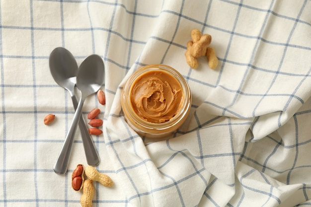 Napkin with peanut jar of peanut butter and spoons Premium Photo