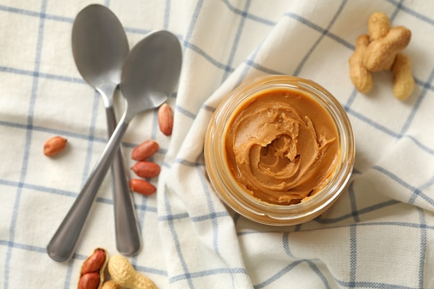 Napkin with peanut jar of peanut butter and spoons