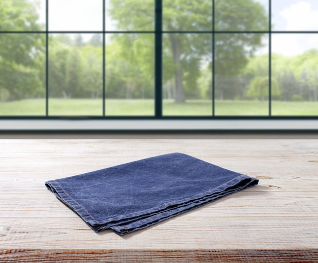 Napkin on wooden table perspective. summer landscape outside the window.