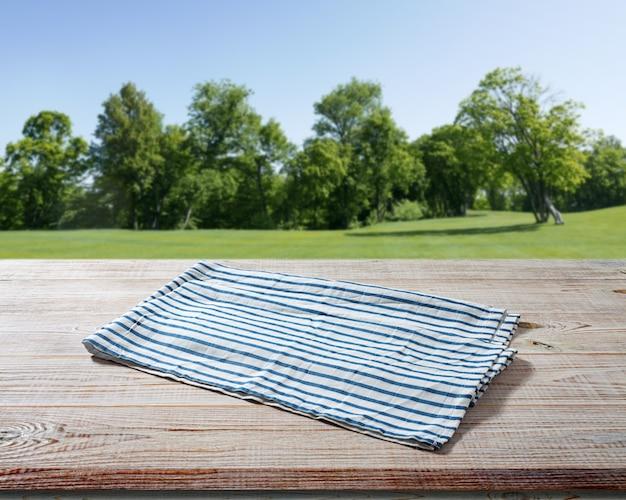 Napkin on wooden table perspective. summer landscape