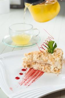 白いプレートに赤いチョコレート、ミント、ベリージャムのスパイラルで飾られたナポレオンケーキ