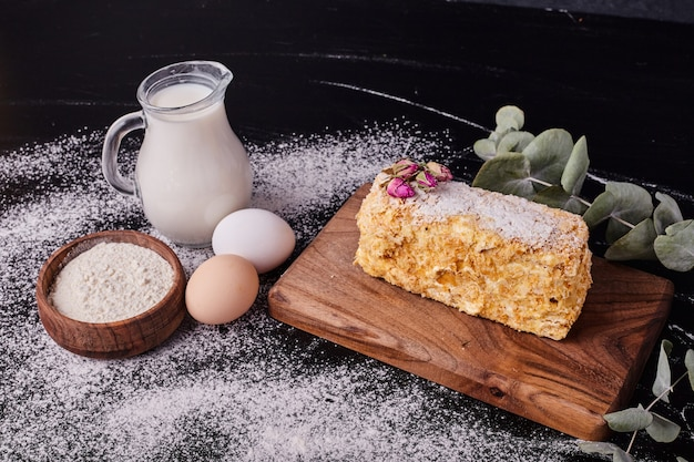 Torta napoleone decorata con semi di fiori secchi sulla tavola nera con uovo, latte e ciotola di farina.