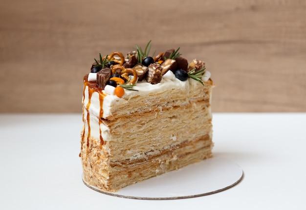 Торт наполеон в разрезе, кусок торта, украшенный ягодами, шоколадом и конфетами на белой поверхности