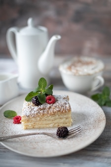 Napoleon dessert in a plate with berries and mint, with a cup of cappuccino on a wooden table.