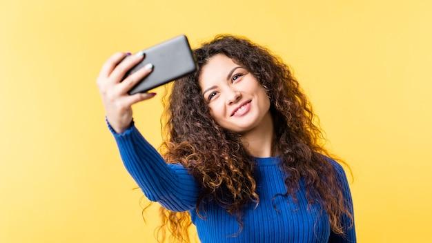 Нарциссическое поведение. зависимость от социальных сетей. молодая леди, принимая selfie на смартфоне, улыбаясь в камеру.