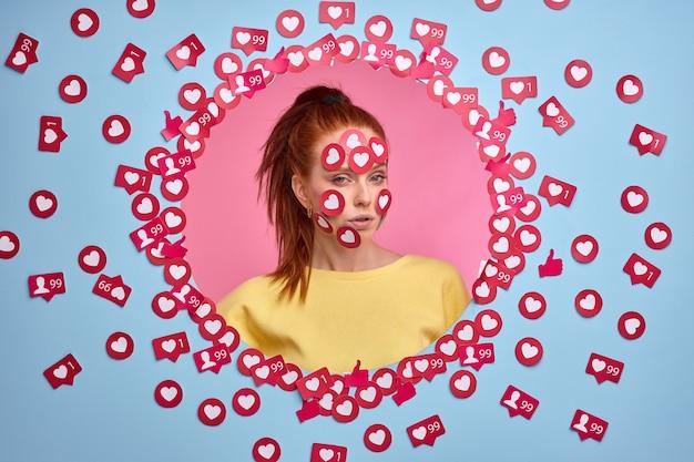 Нарциссическая женщина любит внимание в интернете. портрет рыжей женщины в повседневной одежде среди кнопок любит.
