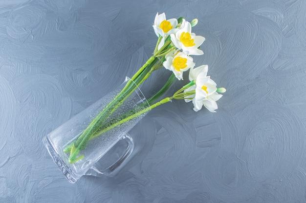 白いテーブルの上のガラスの水差しの水仙。