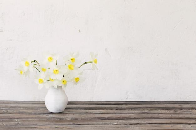 木製のテーブルの上に花瓶の水仙