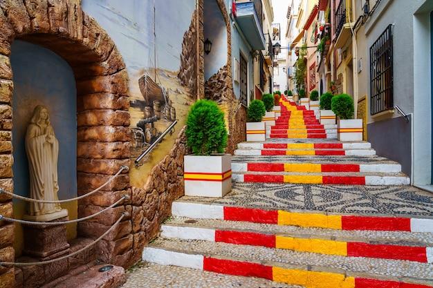 階段にスペイン国旗が飾られた狭い路地。カルペアリカンテ。