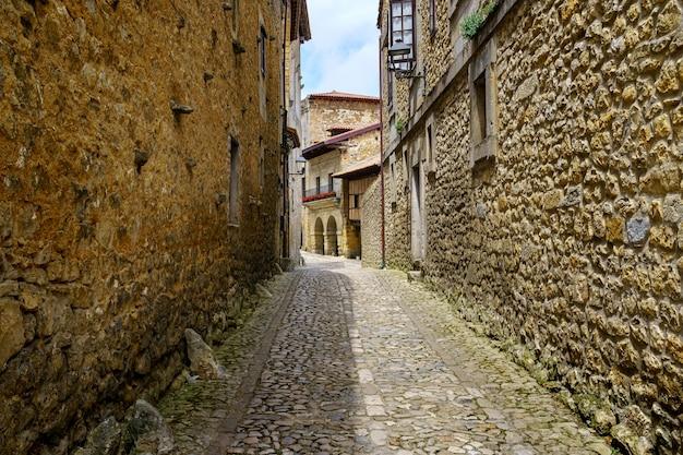 Узкая аллея со старинными каменными домами и арками средневековых построек