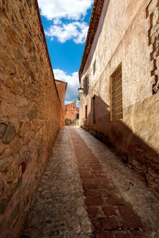 Narrow alley with old stone houses in medieval style in the town of albarracã­n, teruel aragã³n. spain