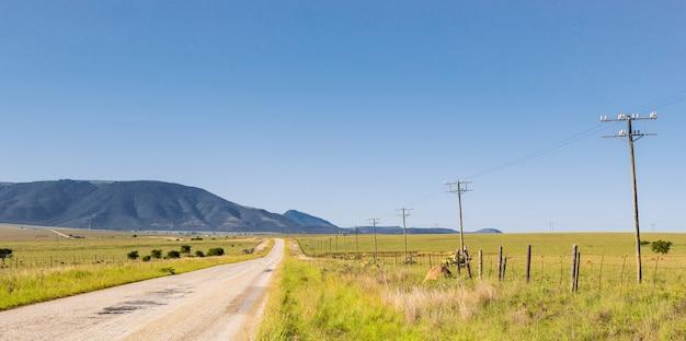 高圧線に接続された長い列の送電鉄塔がある、田舎の狭いアスファルト道路