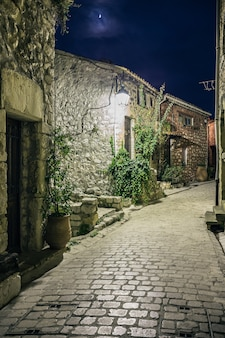 夜、フランスの古い村の花と狭い石畳の通り。