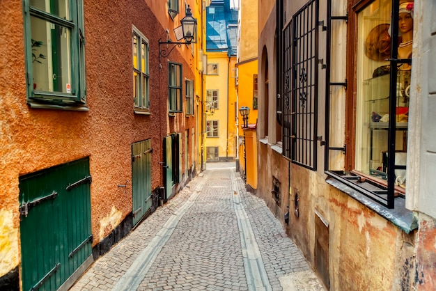 The narrow cobblestone street with medieval houses of gamla stan historic old center of stockholm at summer sunny day.