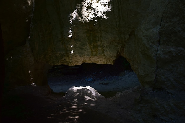 Узкий вход в подземную пещеру или грот, слабо освещенный солнечным светом.