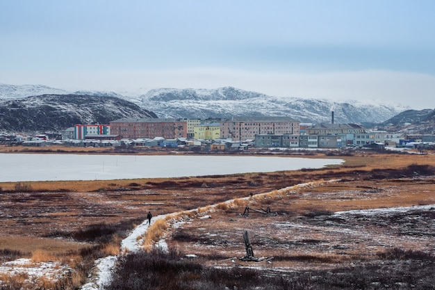 A narrow path that goes into the distance to the arctic village located between the polar hills.