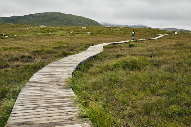 Narrow pathway in connemara national park in ireland under a cloudy sky