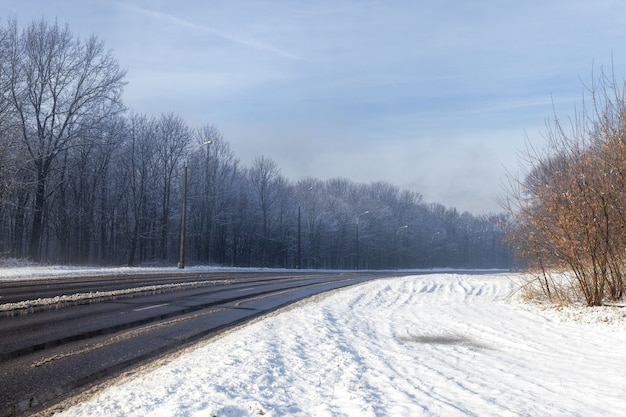 Narrow paved snow-covered winter road for car traffic